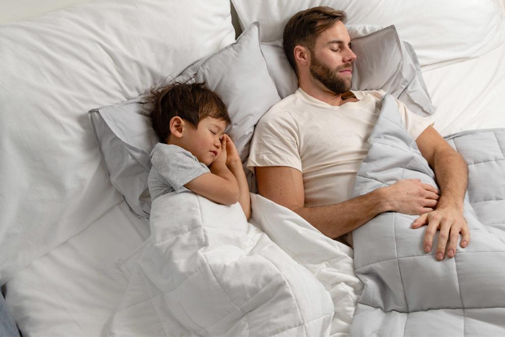 far og sønn sover med hver sin cura pearl vektdyne i ulik farge (grå og hvit)